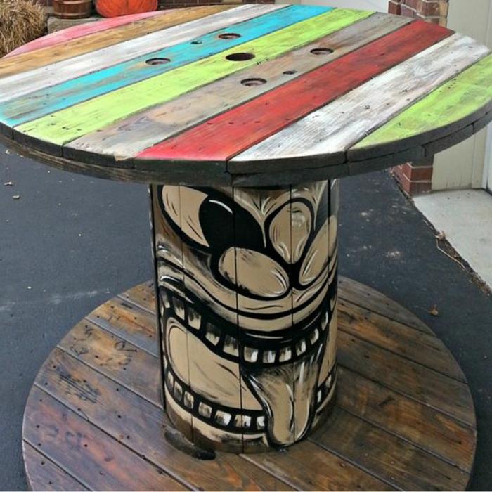touret deco, table plateau, repeinte de rayures de couleurs diverses, un dessin graffiti, deco exterieur interessante