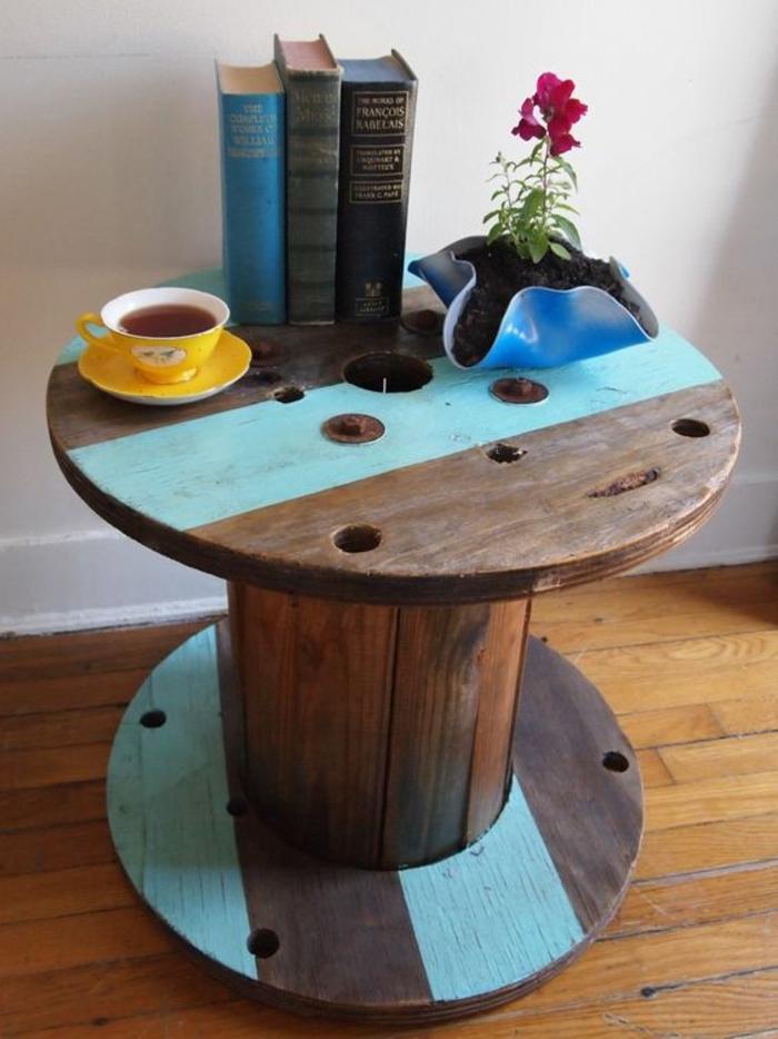 idée comment customise une table en touret, peinture rayures bleues, bous brut, livres, pot de fleur en vinyle et tasse à thé