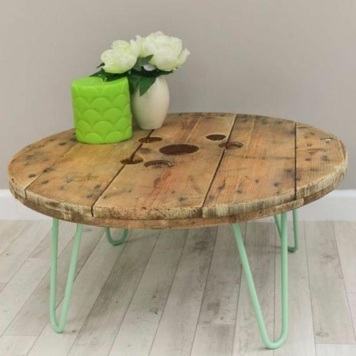 table en touret, plateau en bois, et pied en épingle à cheveux, bougie verte et vase avec un bouquet de fleurs blanches, parquet gris blanc