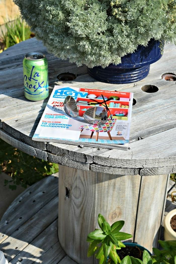deco exterieur, amenagement jardin, table en touret grise, magazine, plante verte