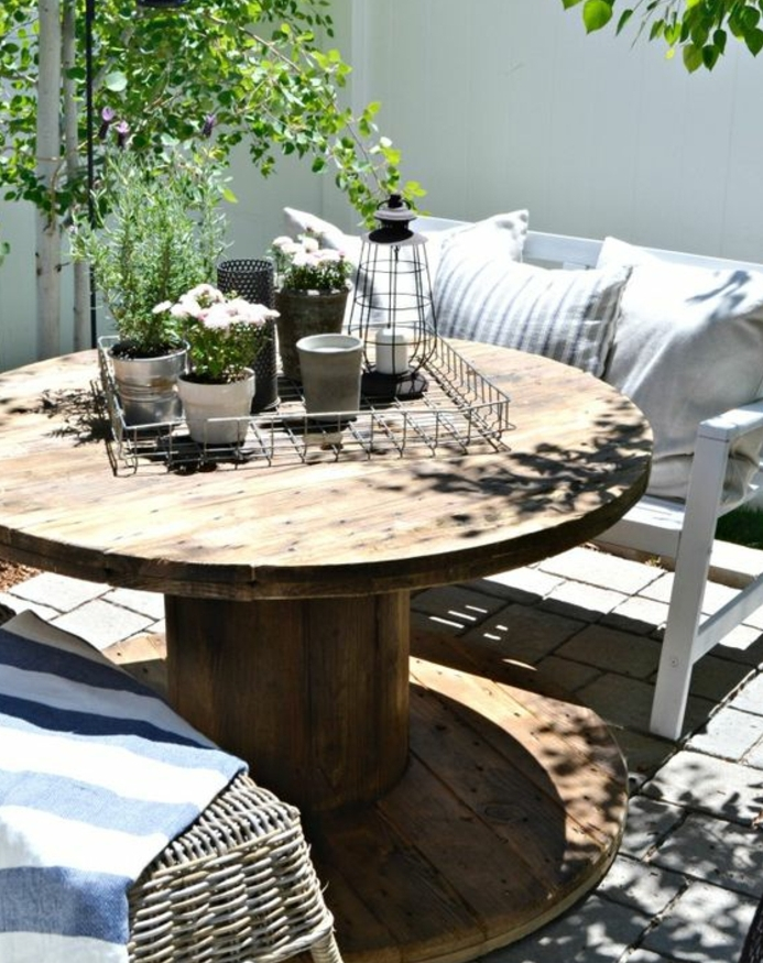 amenagement jardin, table en touret bois marron, banc blanc, coussins decoraifs, centre de table floral vintage, chaise en rotin