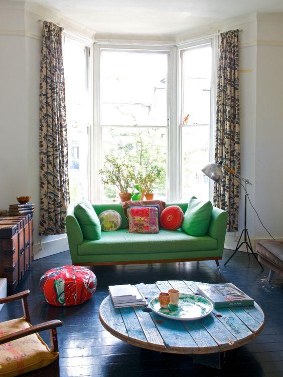 idée comment aménager un salon moderne, table en touret, plateau en bois bleu, parquet bleu foncé, canapé vert, coussins multicolores