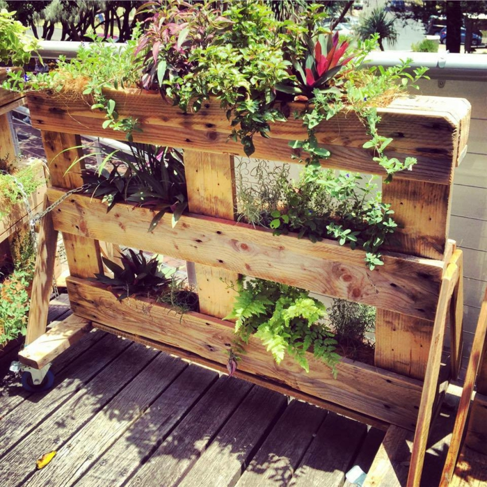 jardiniere palette avec des fleurs plantées dedans sur une terrasse en teck, des plantes de genre dfférent