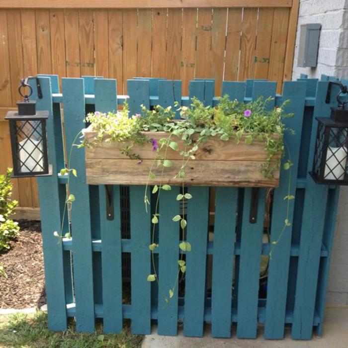 bac a fleur en palette simple avec des plantes, sur une palissade couleur bleu canard, lanternes et bougies, deco jardin exterieur