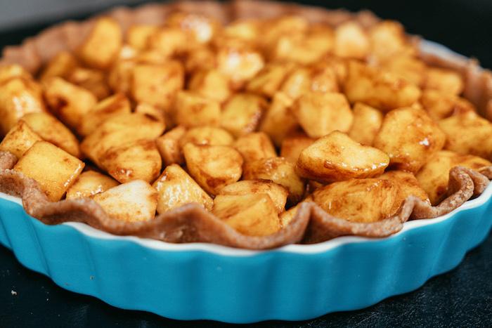 mettre les pommes coupés en dés dessus la pâte, repas léger constitué de dessert équilibré, tarte aux pommes à la cannelle et épices d automne