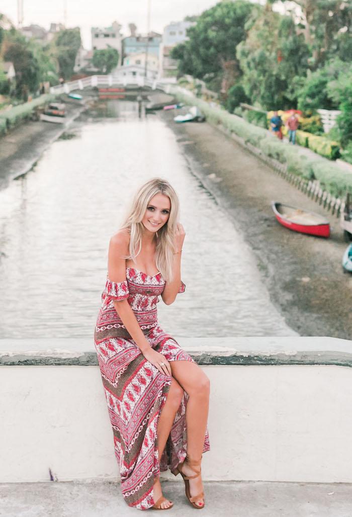 robe bohème chic, pont, femme blonde, bague, pédicure rouge, robe avec manches tombantes