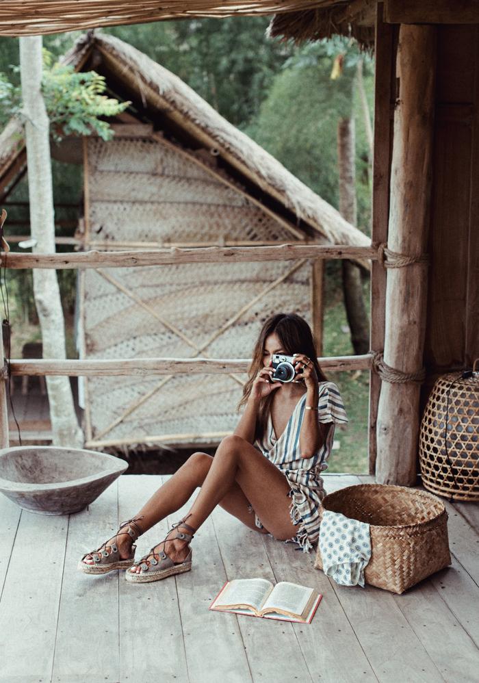 robe bohème chic, livres, maison en bois, appareil photo vintage, sandales avec lacets