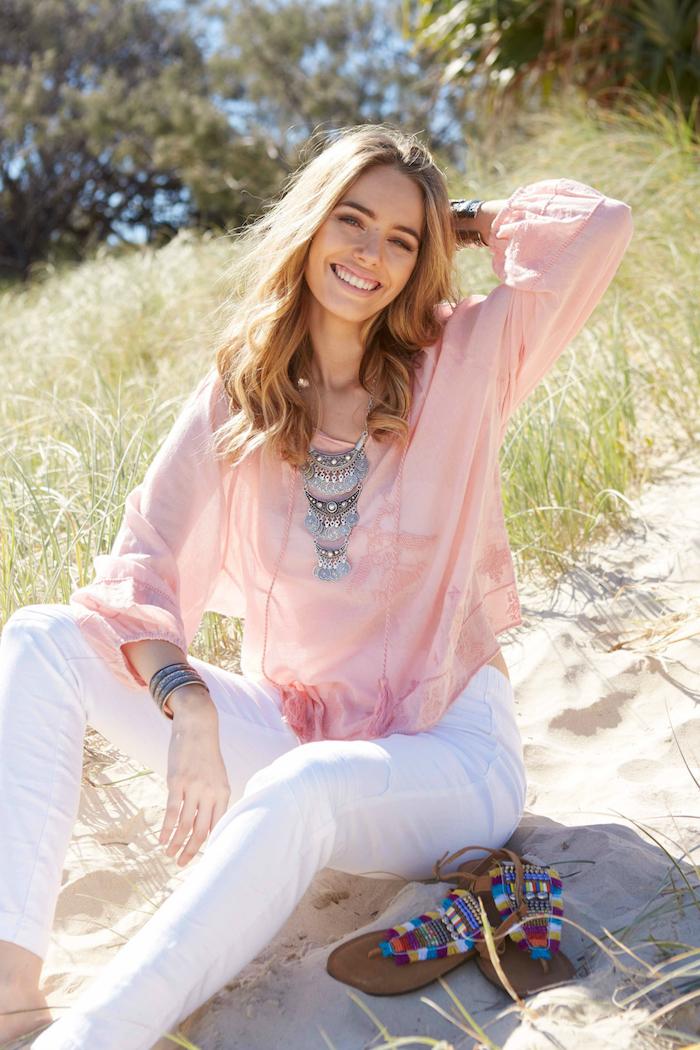 style bohème, cheveux bouclés, rouge à lèvres rose, bracelet métallique, pantalon blanc, chemise rose, look bohème