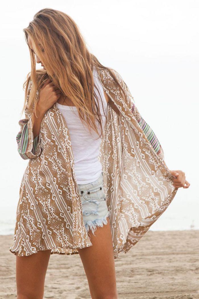 look bohème, femme sur la plage, cheveux châtain cuivré, débardeur blanc, shorts en denim