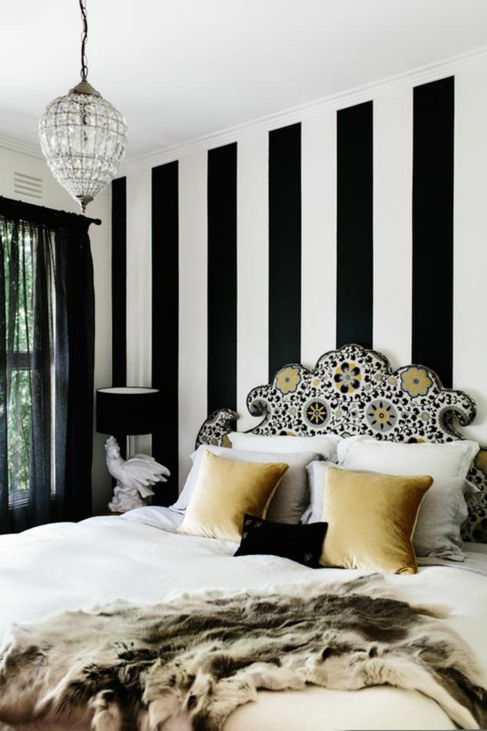 déco chambre adulte avec les murs aux rayures noires et blanches lustre en vrystal dossier du lit richement orné en motifs floraux colorés