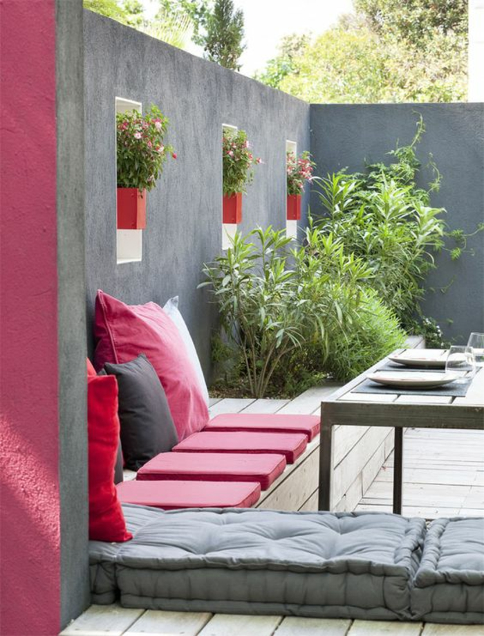 couleur magenta dans une terrasse couverte avec des meubles d exterieur et des murs gris