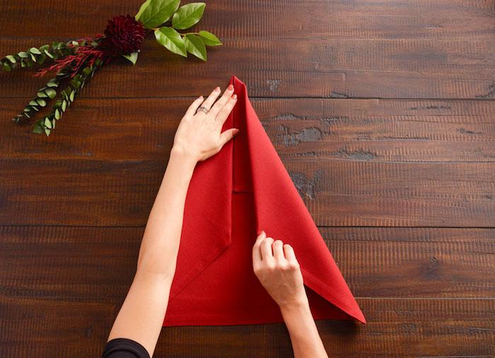 déco de noel, guide pour plier une serviette, bouquet de feuilles verte et fleur rouge, manucure orange