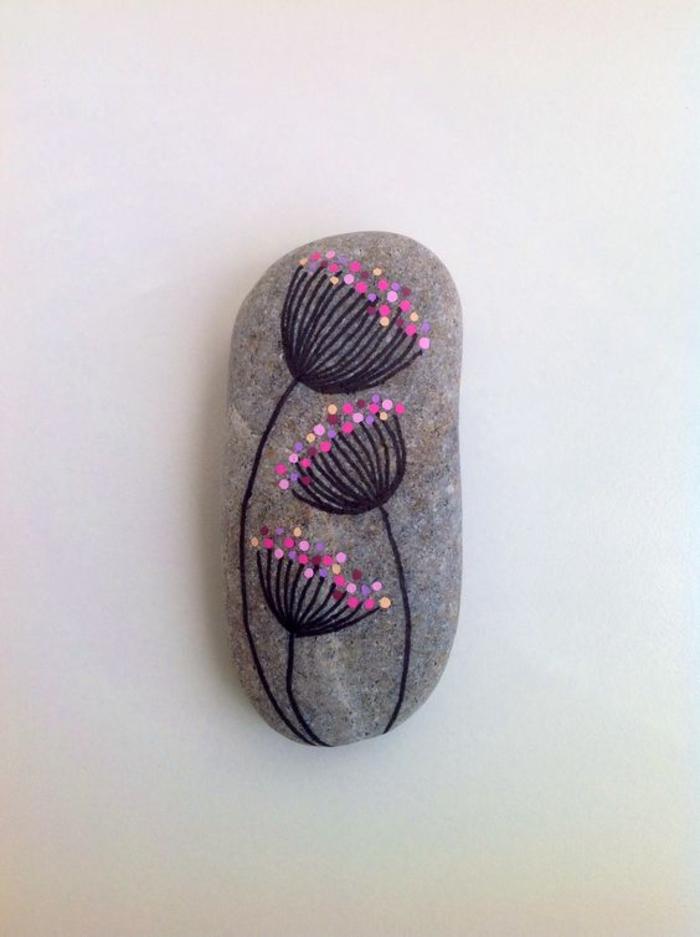jolies fleurs stylisés dessinées sur un galet poli gris, un bricolage enfant qui stimule la créativité et l'imagination