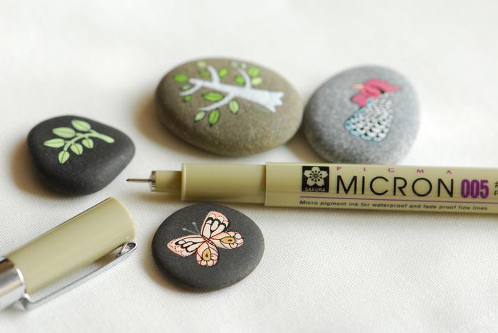 de jolis dessins minuscules au marqueur à pointe fine réalisés sur galets nature, idée créative pour activité manuelle adulte