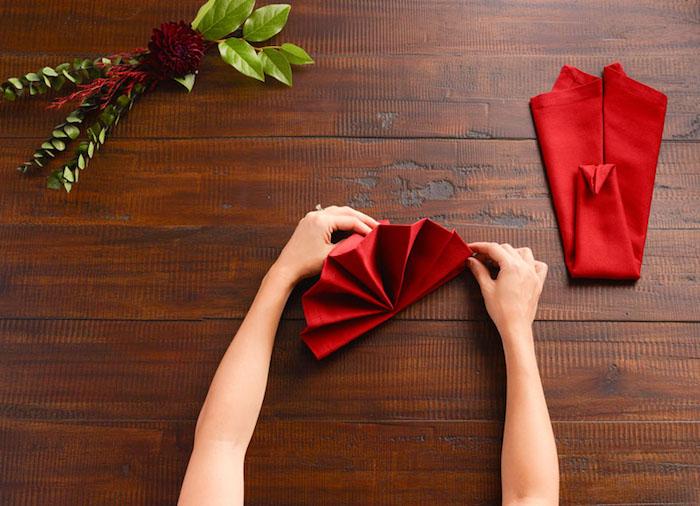 diy deco de table de noel, technique origami avec nappe de table rouge, activité manuelle pour femme