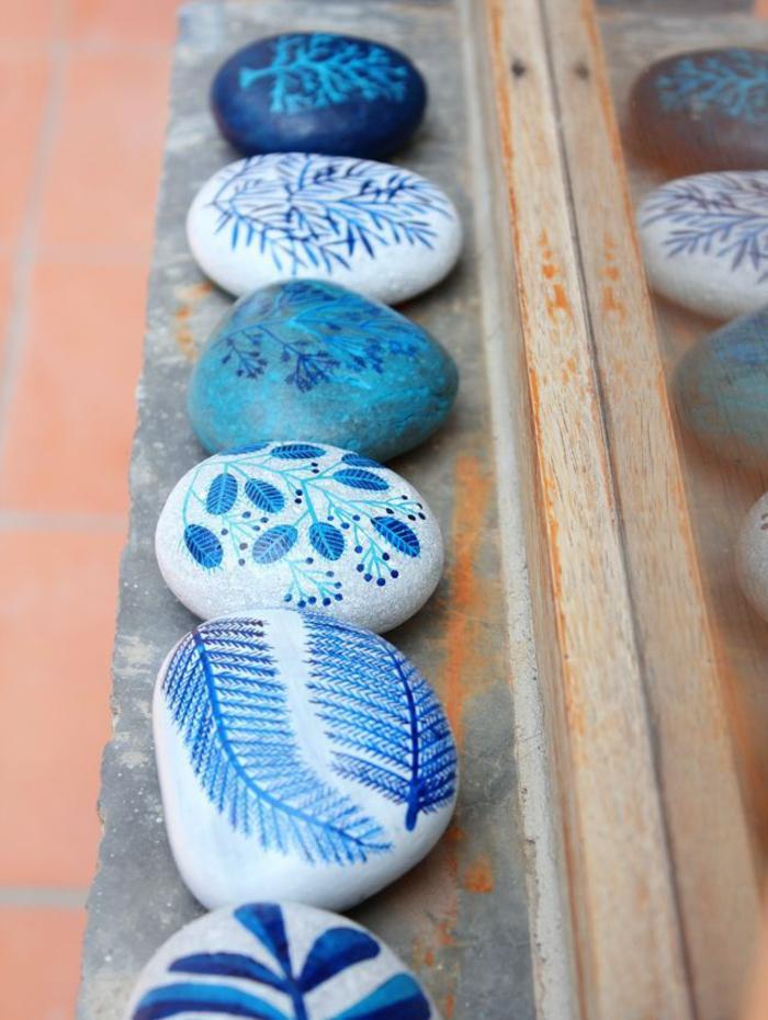 une jolie idée déco avec des galets peints à motifs végétaux aux nuances de bleu