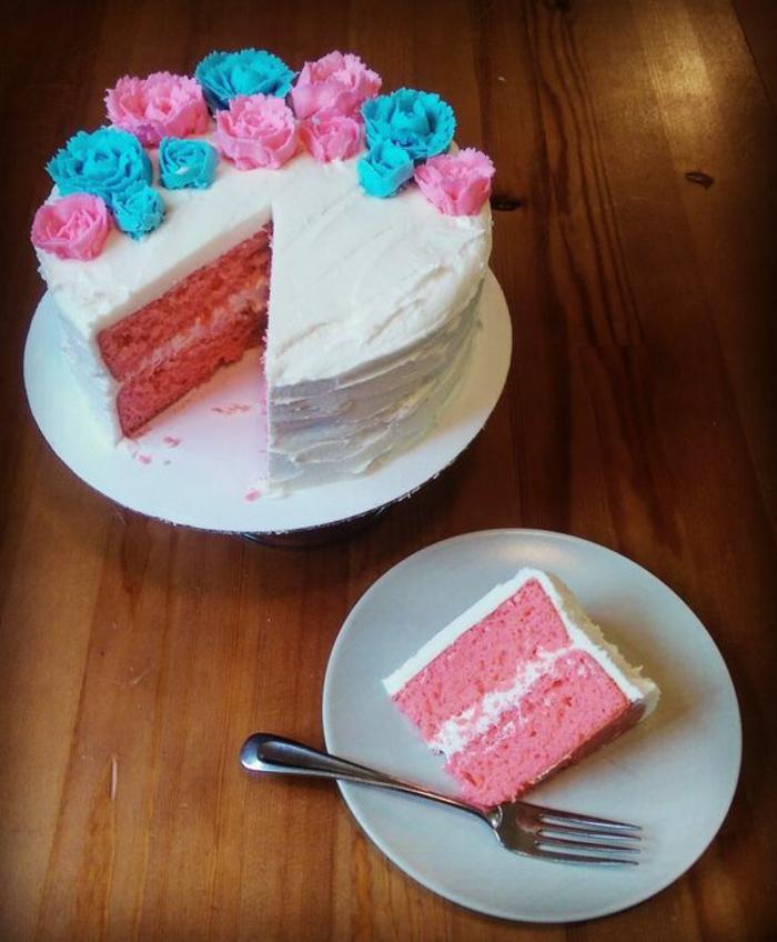 Un gâteau rose ou bleu couverte de fondant blanc pour comprendre le sexe du bébé avec surprise