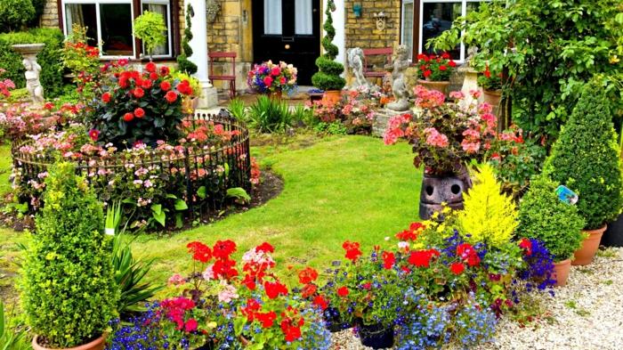 idee deco jardin, parterre de gravier, gazon vert parterre de fleurs colorés, sculptures statues jardin