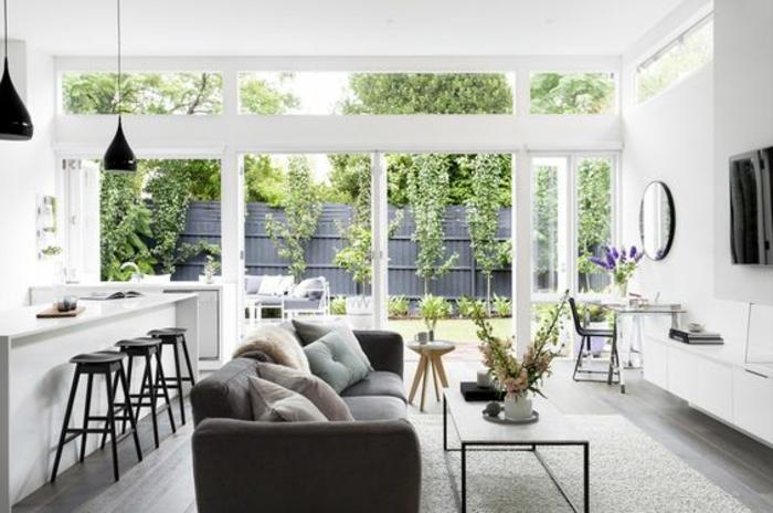aménager une petite cuisine, façade cuisine blanche avec bar blanc et tabourets noirs, parquet gris, canapé gris et table minimaliste, tapis et meuble tv blanc