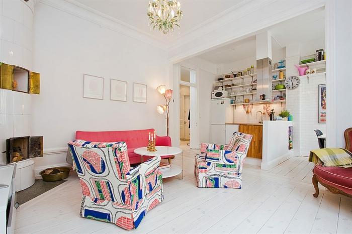 petite cuisine americaine blanche avec porte placard en bois, etagères de rangement, ouverture sur un salon, parquet blanchi, canapé rose saumon, fauteuils colorés, cheminée design