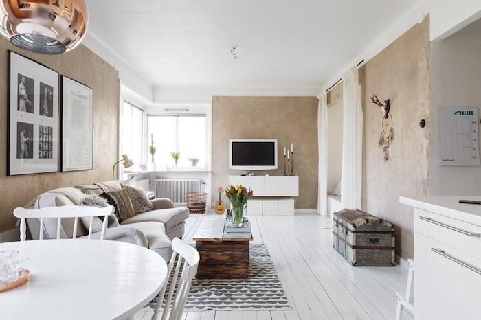 intérieur scandinave, parquet en bois peint en blanc, table basse en bois avec vase et tulipes, canapé beige en cuir