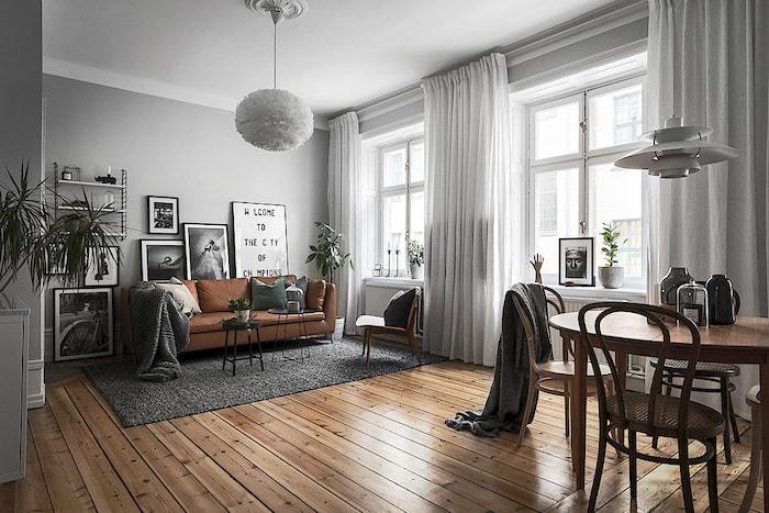tableau scandinave, murs peints en gris, rideaux longs en blanc, tapis rectangulaire en gris, canapé en cuir marron