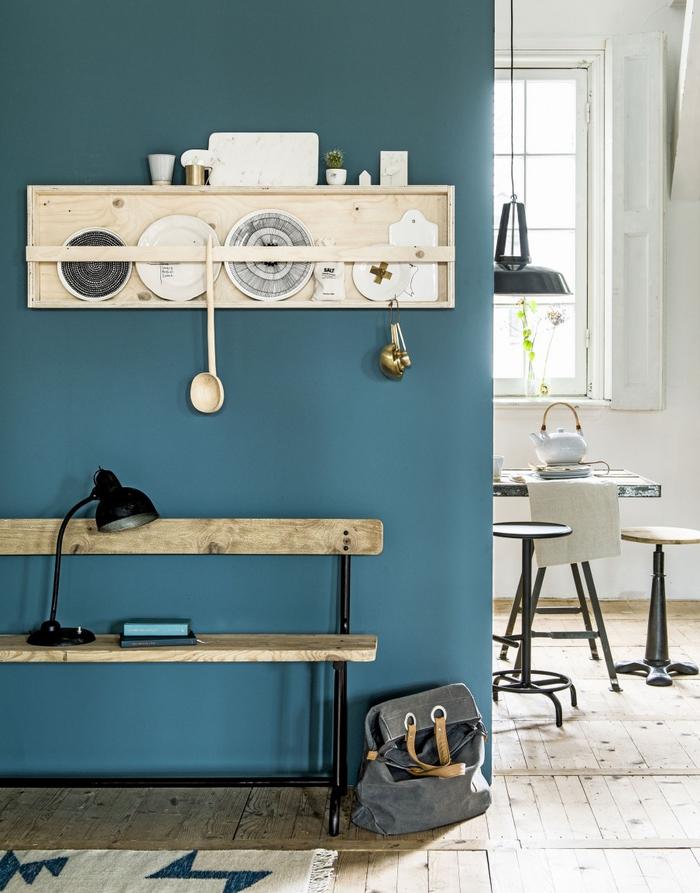 un pan de mur couleur canard en joli contraste avec l'intérieur en blanc et le bois clair, une ambiance de style scandinave très apaisante