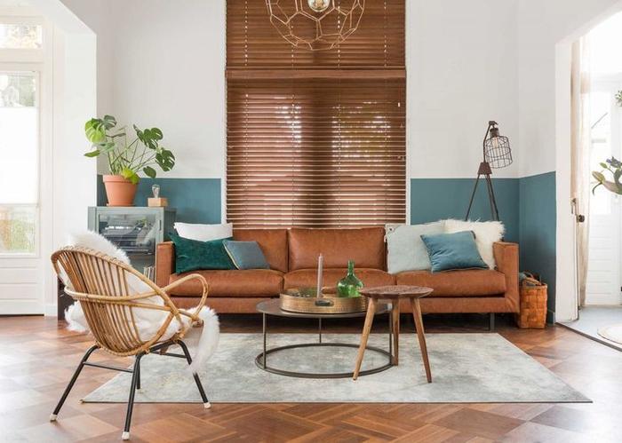 ambiance cozy d'un salon bohème chic aux couleurs naturelles et aux tons de vert canard