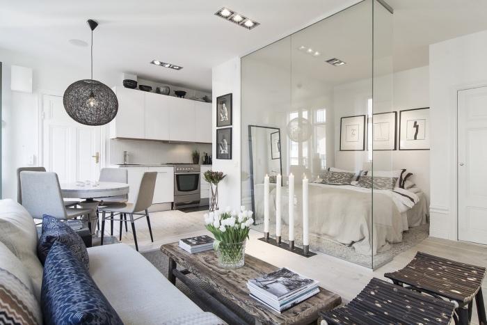 idée comment aménager un studio, façade cuisine blanche ouverte sur une salle à manger salon avec canapé blanc et table basse en bois brut, tabourets en bois intéressants, chandelier, chambre séparée par une verrière