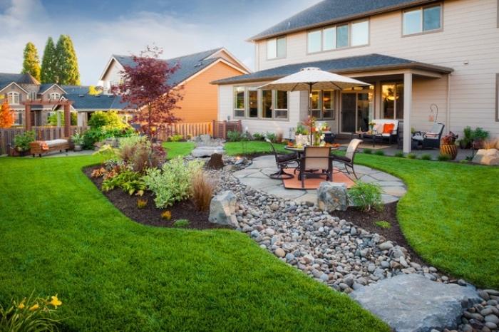 idée de génie jardin, gazon avec patio, chemin de pierres, quelques arbustes, salon de jardin en table et chaises avec parasol