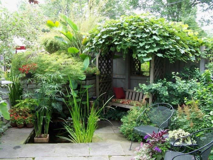 idee amenagement jardin, espace repos avec un banc en bois avec une arche végétalisée, chaises en metal, terrain en dalles de pierre, plusieurs p;antes vertes