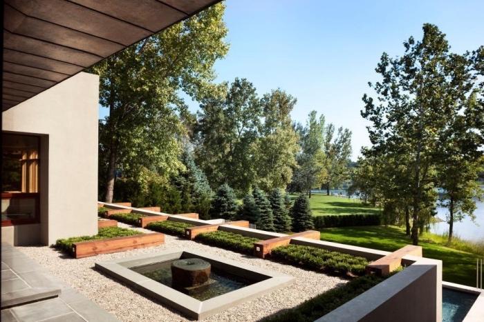 amenagement jardin paysager, terrasse revêtement de gravier avec fontaine d eau et bassin, un gazon avec des buis et arbres, petite piscine d eau