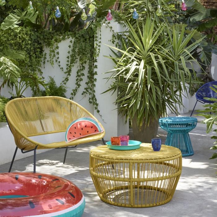 idée pour aménager son jardin, salon de jardin tressé avec un canapé, table et tabouret, palmier dans un pot de fleur plantes grimpantes, motif pastque