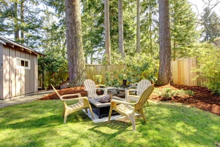 idee jardin amenagement, brasero, cheminée exterieure, chaises en bois, grands arbres, palissade en planches de bois, cadre forestier