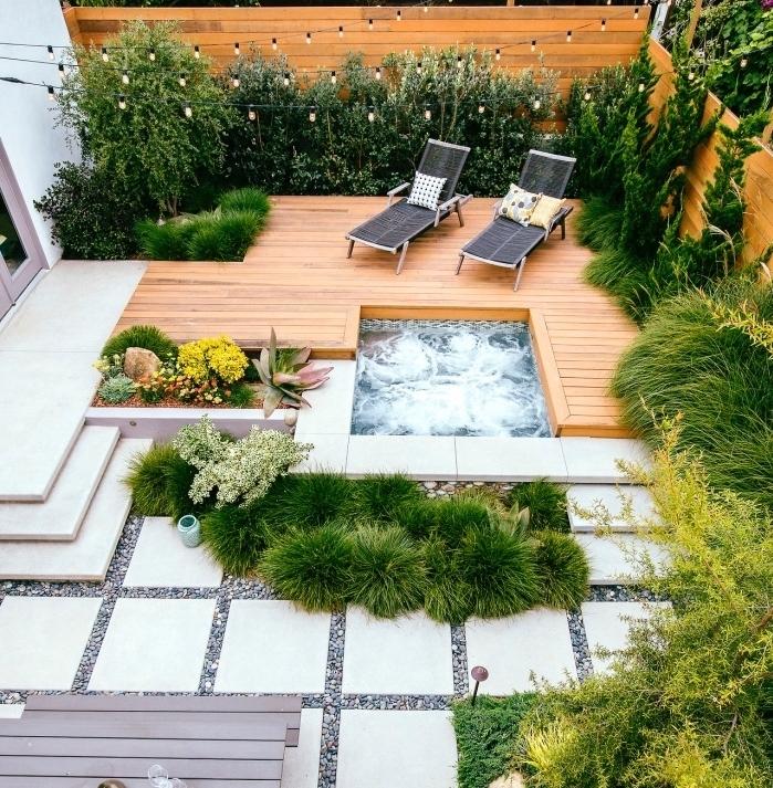 aménager son jardin, gravier, dalles de béton et terrassé en teck, petit bassin d eau, chaise longue, arbustes vertes autour d'une clôture en bois, plusieurs fleurs
