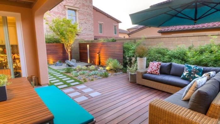 salon de jardin sur une terrasse en teck, canapé en rotin avec coussins d assise gris, table en bois, petit jardin sec en gravier et arbustes, pierres, arbre vert