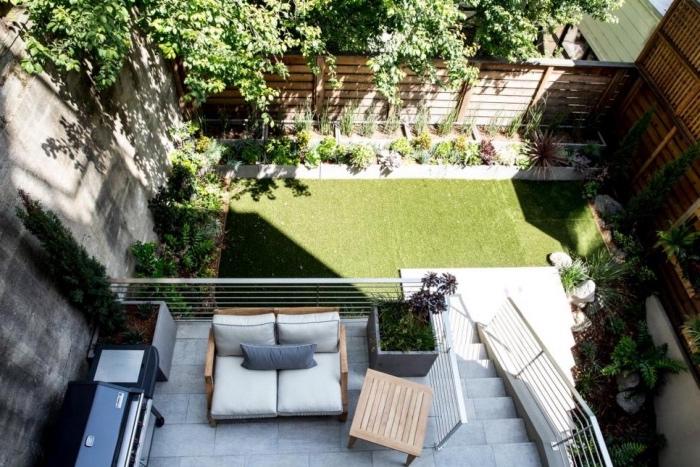 une terrasse en béton avec cuisine d été, barbecue fauteuil en bois et plants dans des pots en beton, gazon avec bordure d arbustes