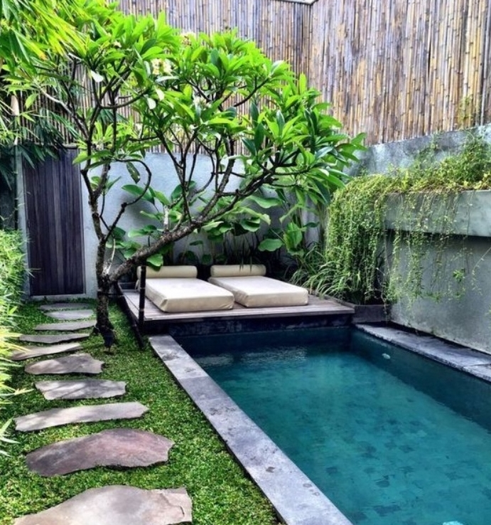 idee deco ajrdin zen japonais avec un petit bassin d eau, chemin de peirres sur un gazon vert, arbre à couronne verte, bambou, matelas îlot coin détente