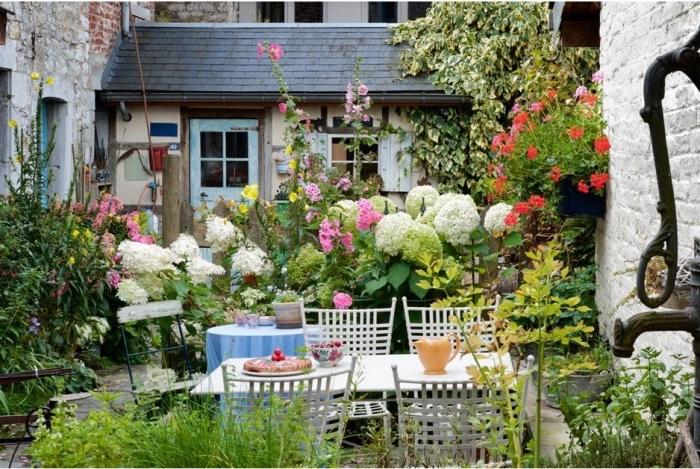 amenagement petit jardin fleuri avec beaucoup de fleur et d arbustes fleuris et plantes grimpantes, coin repas a l exterieur avec table et chaises blanches