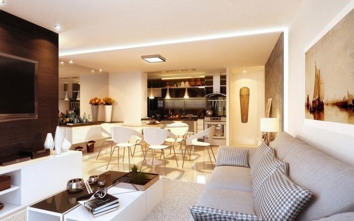 cuisine americaine ouverte en inox, table et chaises blanches, sol carrelage beige, canapé et tapis gris, table basse en noir et blanc, deco africaine et tableau decoratif