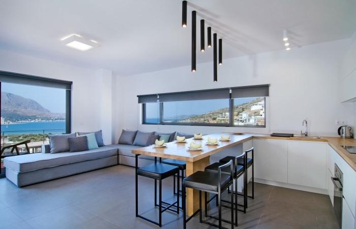 cuisine ouverte sur salon, façade cuisine blanche avec plan de travail en bois, carrelage gris, table et chaises noires, canapé d angle gris, suspension originale