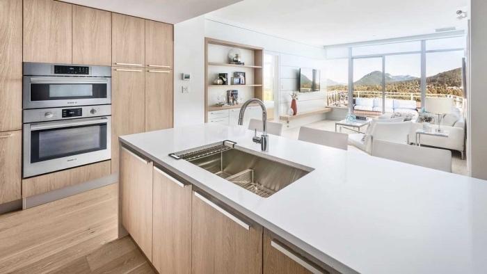 cuisine ouverte sur salon, façade cuisine et portes ilot en bois clair, plan de travail blanc avec des chaises blanches, ouverture sur salon table basse canapé et fauteuil blanc
