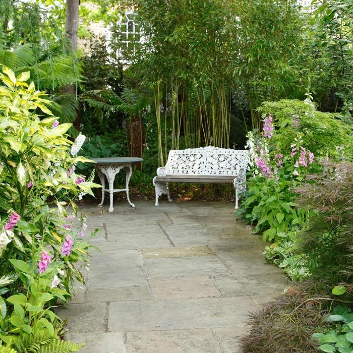 paysager son jardin, un espace revêtement en pierres, banc vintage blanc et table ronde de jardin, bambou et plusieurs arbustes fleuris