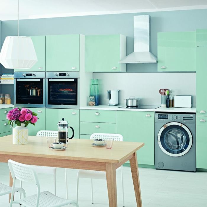 idée comment aménager une cuisine vintage moderne, façade cuisine couleur vert d'eau sur le fond d un mur bleu pastel, table en bois et chaises en métal, lustre design intéressant