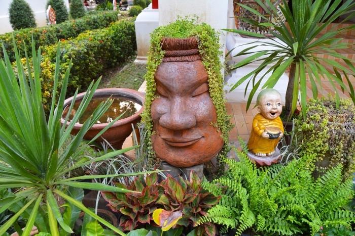 amenagement jardin zen, statues japonaises, une fontaine d eau, buis, arbustes et palmier, idee deco exterieur exotique