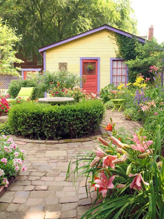 amenagement petit jardin avec des chemins de pierre, une fontaine entouré de buis, parterre de fleurs, chaise longue dans la cour d une petite maison de campagne
