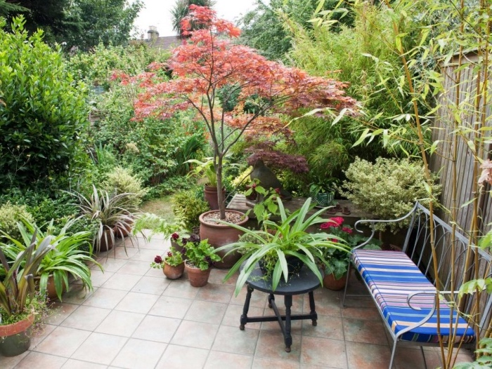 idee amenagement jardin avec un terrain patio salon de jardin, revêtement carrelage, plusieurs arbres, arbustes, fleurs, deco à l anglaise, banc en metal a coussin multicolores