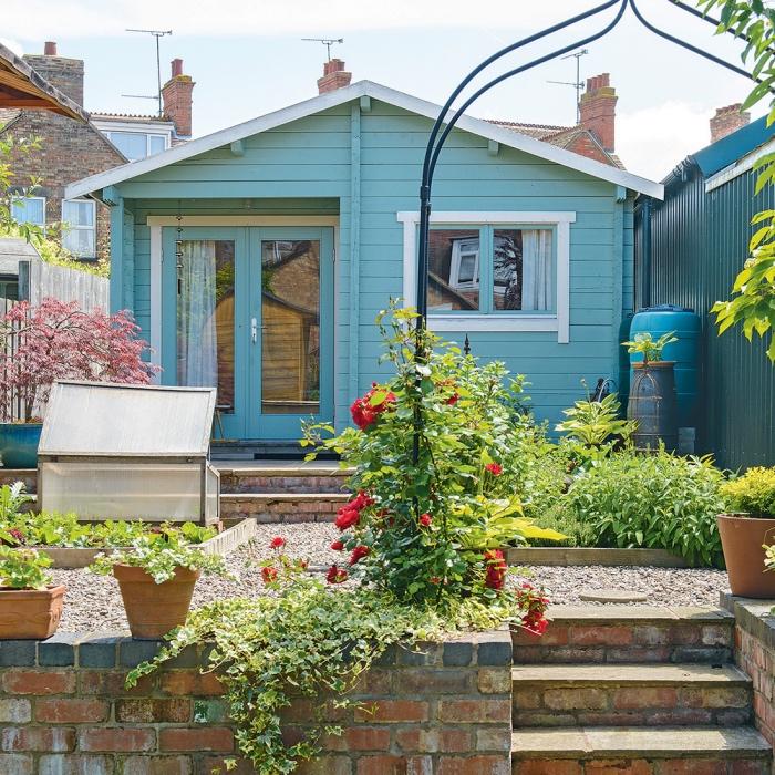 idee jardin amenagement, terrasse surélevée, gravier et carré potager entrée en arc en métal avec des fleurs, petite maison bleue de campagne