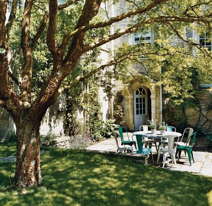 idee jardin avec gazon et grand arbre, patio et salon de jardin avec table et chaises en metal, lierre qui grimpe sur le mur d une maison campagne vintage