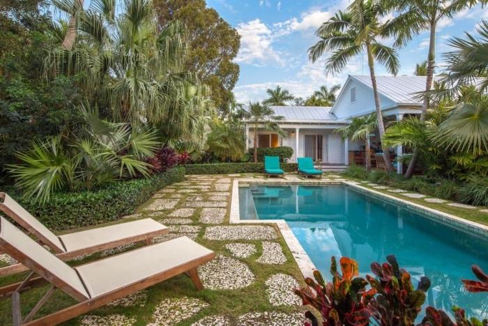idee amenagement jardin avec piscine, chaise longues en bois, buis, grands arbres et palmiers, maison d été, végétation abondante, décor extérieur exotique tropical